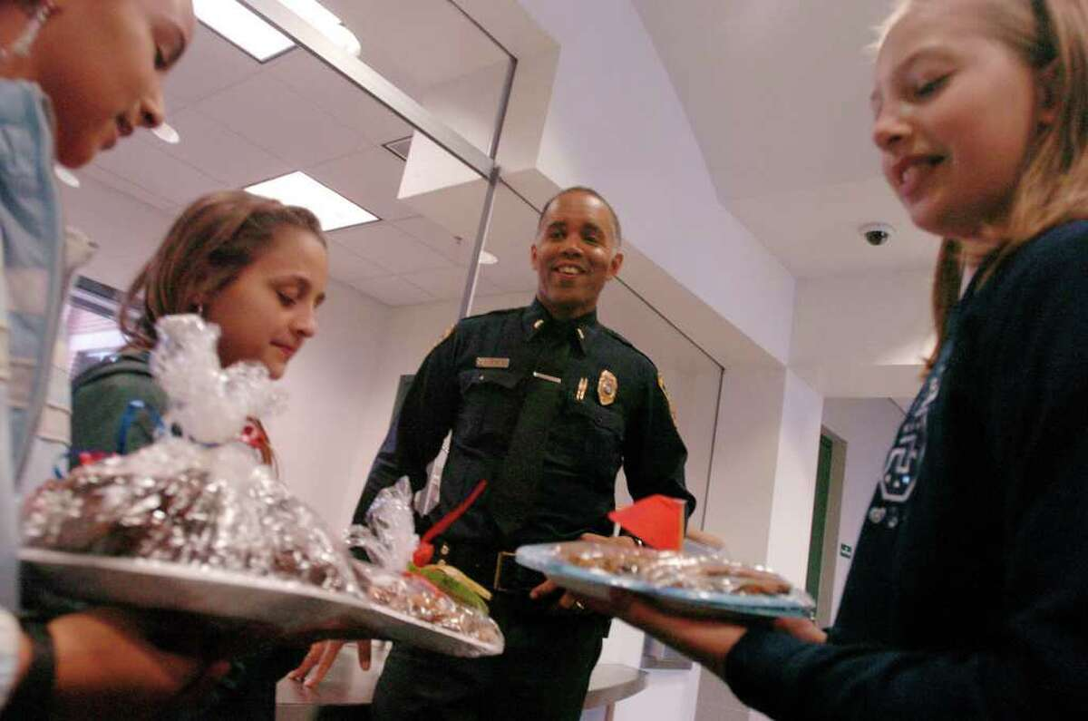 Norwalk_050605_ Norwalk Police Lt. Peter Randall greets Side by Side Community School students (L to R) Aja Piro, Kayla Benincaso and Rhianna Seferian as a group from the school deliver baked goods to the new police station. Kathleen O'Rourke/staff photo