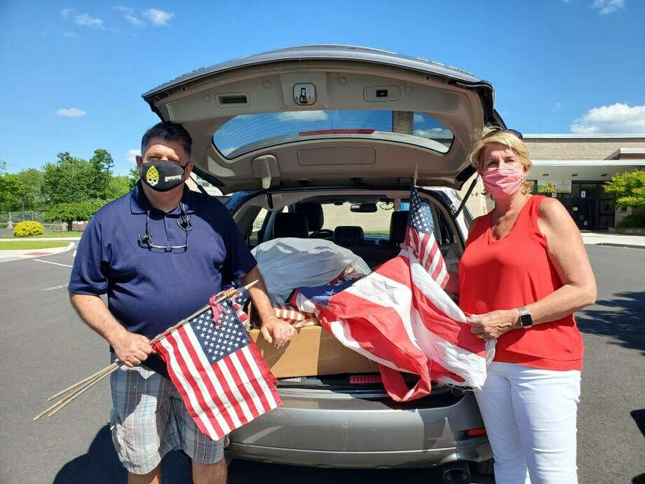 State Reps. Dave Rutigliano (R-123) and Laura Devlin (R-134) are standing in front of a car full of worn and tattered flags collected on Saturday, June 13, during their fourth annual flag collection, in cooperation with the Trumbull American Legion Post #141. For this year's flag collection, the lawmakers observed social distancing practices with a car drop-off at Middlebrook Elementary School. The flags will be given to the American Legion for proper retirement. Photo: Contributed Photo