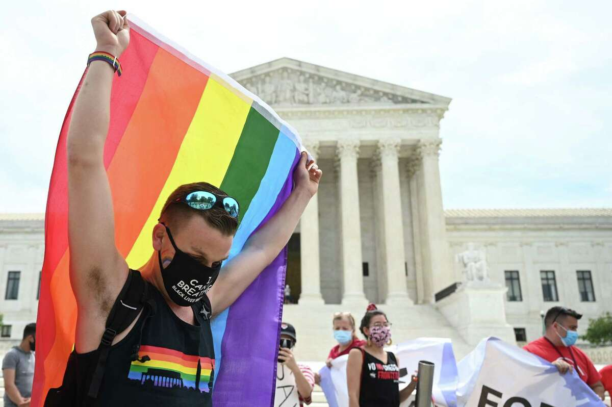 A man waves a rainbow flag in front of the US Supreme Court that released a decision that says federal law protects LGBTQ workers from discrimination on June 15, 2020 in Washington,DC. - The US top court has ruled it illegal to fire workers based on sexual orientation. (Photo by JIM WATSON / AFP) (Photo by JIM WATSON/AFP via Getty Images)
