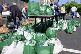 Volunteers pack food into bags that will be distributed to those in need at the Catholic Charities of the Diocese of Albany Pastoral Center on Monday, June 15, 2020, in Albany, N.Y. The food distribution event was put on by the Regional Food Bank of Northeastern New York and the Catholic Charities of the Diocese of Albany. (Paul Buckowski/Times Union)