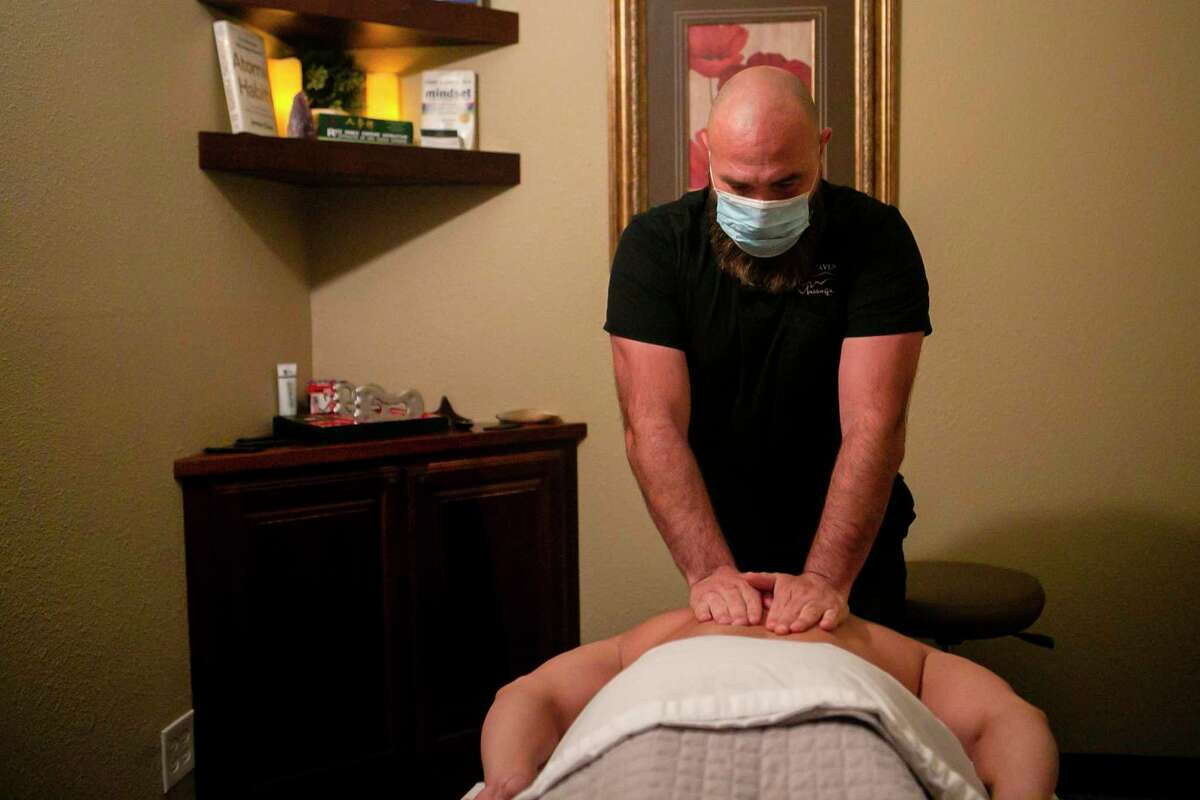 J.P. Baca massages Jesse Piña during Piña's appointment at the Oak Haven Massage on Huebner Road. After a few months without massages, Piña was excited to return for his regular appointments.