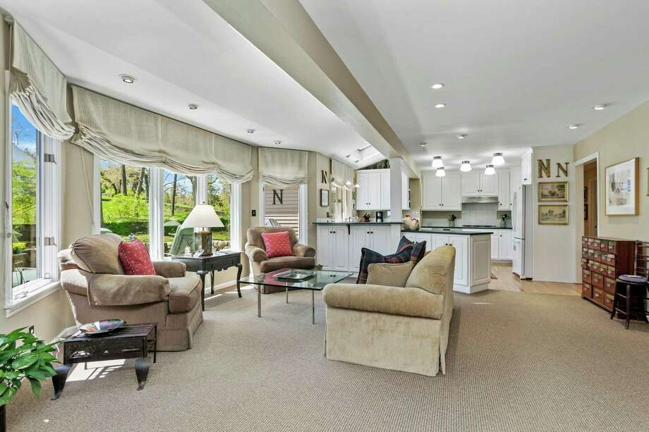 The family room is quite large and features a fireplace against a wall of floor-to-ceiling built-in book and display shelves, a wet bar, vaulted ceiling, skylights, and wall-to-wall carpeting.