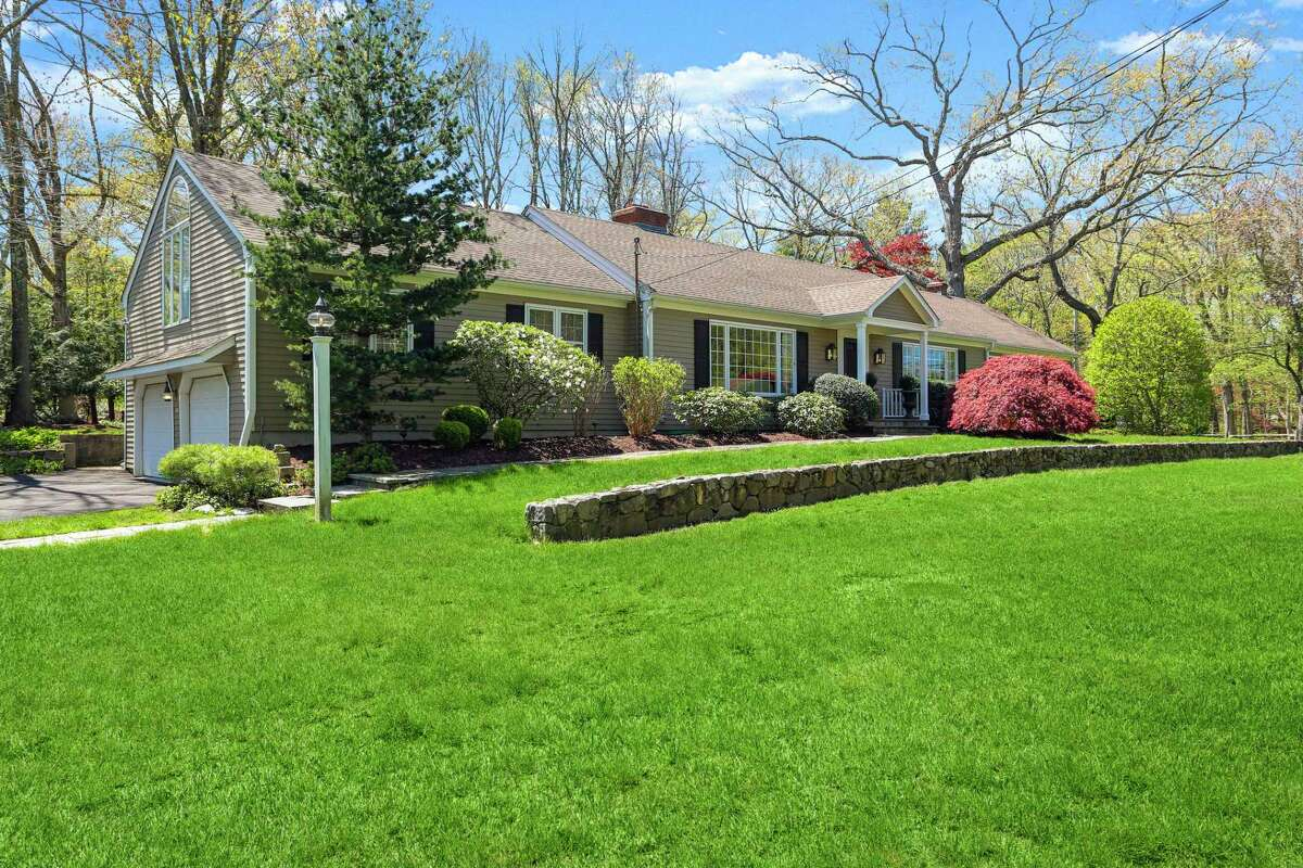A fieldstone wall sits on the front lawn running the length of the house. Behind it is attractive landscaping along the front of the house and a path from the driveway to the front door.