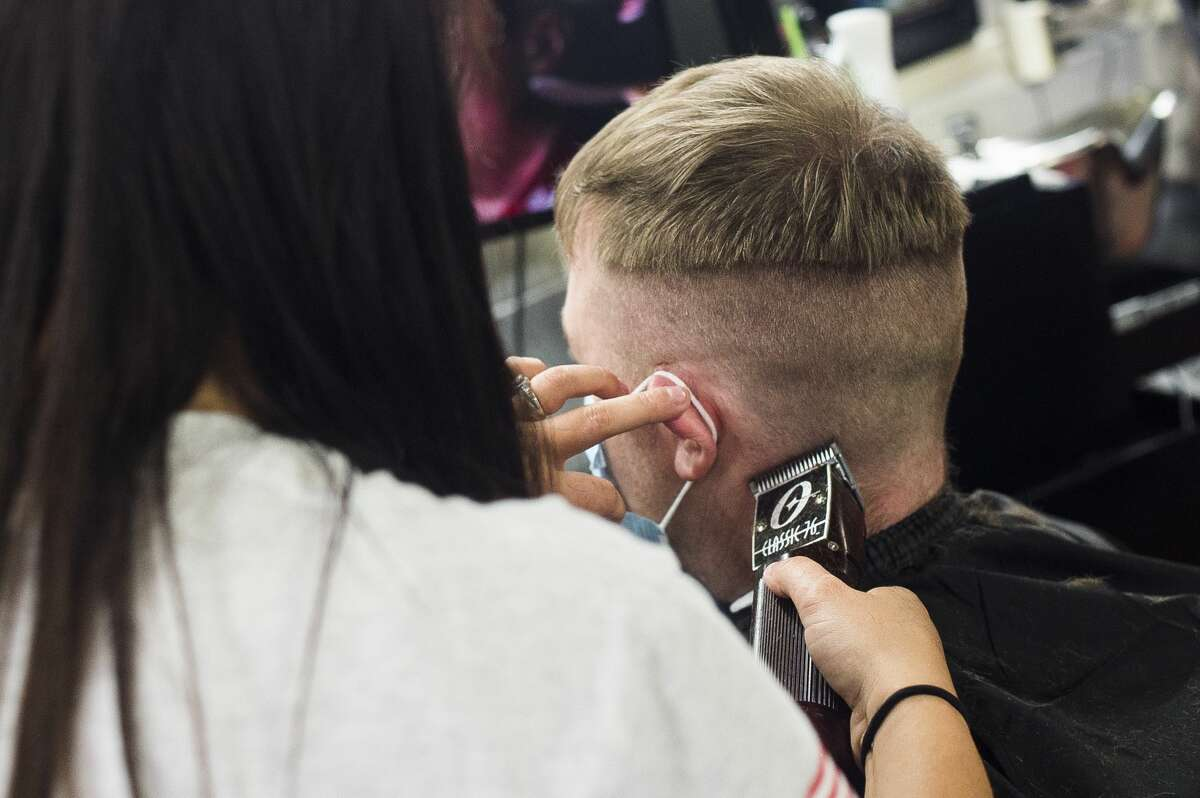 Breanne Fawthrop, a stylist at RJ's All Star Haircuts for Men, cuts Brad Geib's hair inside the shop at 144 Ashman St., one of many barber shops and salons in Midland which opened Monday, June 15, 2020 as restrictions lifted across the state. (Katy Kildee/kkildee@mdn.net)