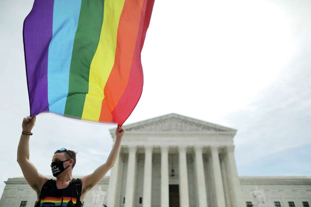 WASHINGTON, DC - JUNE 15: Joseph Fons holding a Pride Flag, stands in front of the U.S. Supreme Court building after the court ruled that LGBTQ people can not be disciplined or fired based on their sexual orientation June 15, 2020 in Washington, DC. With Chief Justice John Roberts and Justice Neil Gorsuch joining the Democratic appointees, the court ruled 6-3 that the Civil Rights Act of 1964 bans bias based on sexual orientation or gender identity.