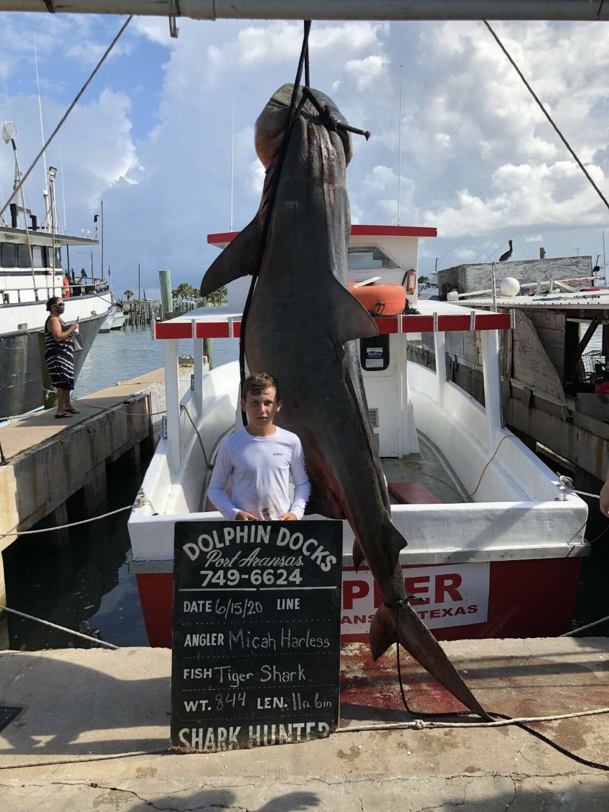 The young angler, Micah Harless, takes a photo with the shark he caught during an offshore trip in Port Aransas.