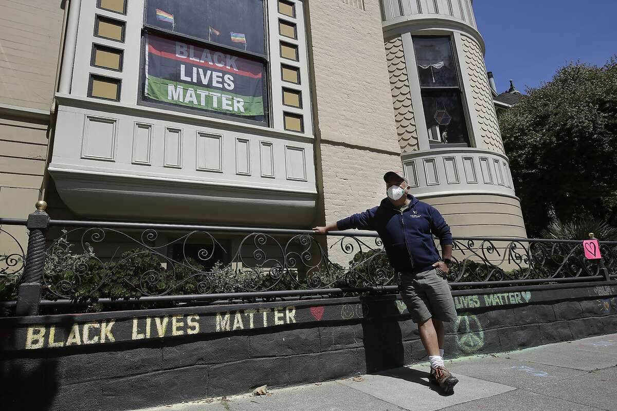 """James Juanillo poses with chalk written outside of his home in San Francisco, Sunday, June 14, 2020. The CEO of a cosmetic company issued an apology Sunday after she and her husband confronted Juanillo and threatened to call police because he stenciled """"Black Lives Matter"""" in chalk on his San Francisco property, as the couple asserted that they know Juanillo doesn't live there and is therefore breaking the law. (AP Photo/Jeff Chiu)"""