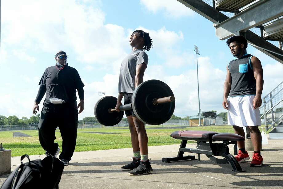 Beaumont United new head coach Marcus Graham watches as Jeremiah Pugh lifts and teammate Johnathan Comeaux spots as summer conditioning begins at Beaumont United Monday morning. While most schools started the summer workouts when the state permitted last week, BISD programs waited until this week to hold camps. Photo taken Monday, June 15, 2020 Kim Brent/The Enterprise Photo: Kim Brent/The Enterprise