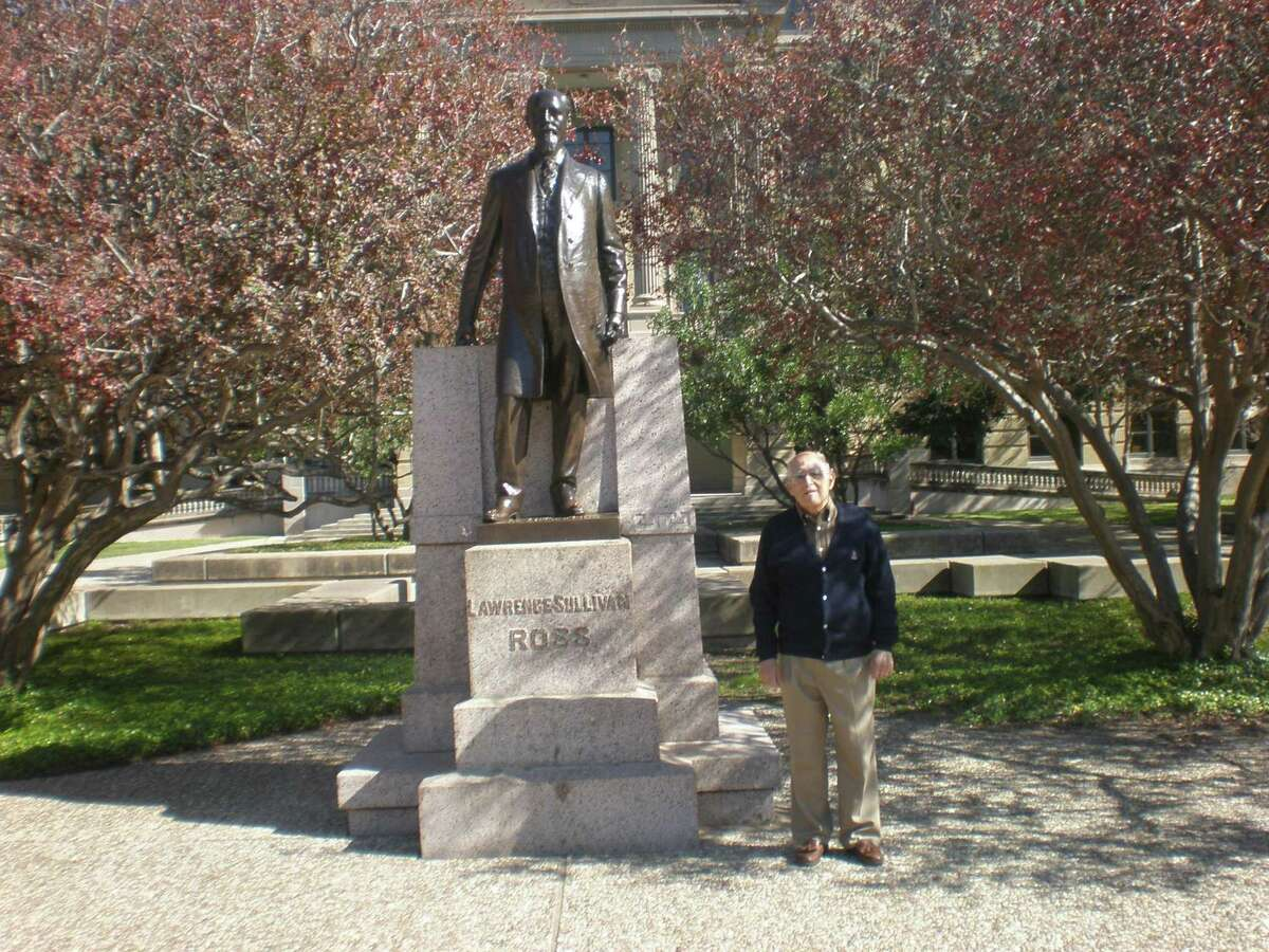 A former student at Texas A&M University poses before the statue of Lawrence Sullivan Sul Ross, one-time president of the school.