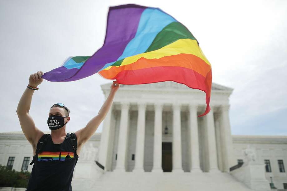 Joseph Fons holding a Pride Flag, stands in front of the U.S. Supreme Court building after the court ruled that LGBTQ people can not be disciplined or fired based on their sexual orientation June 15, 2020 in Washington, DC. Photo: Chip Somodevilla, Getty Images