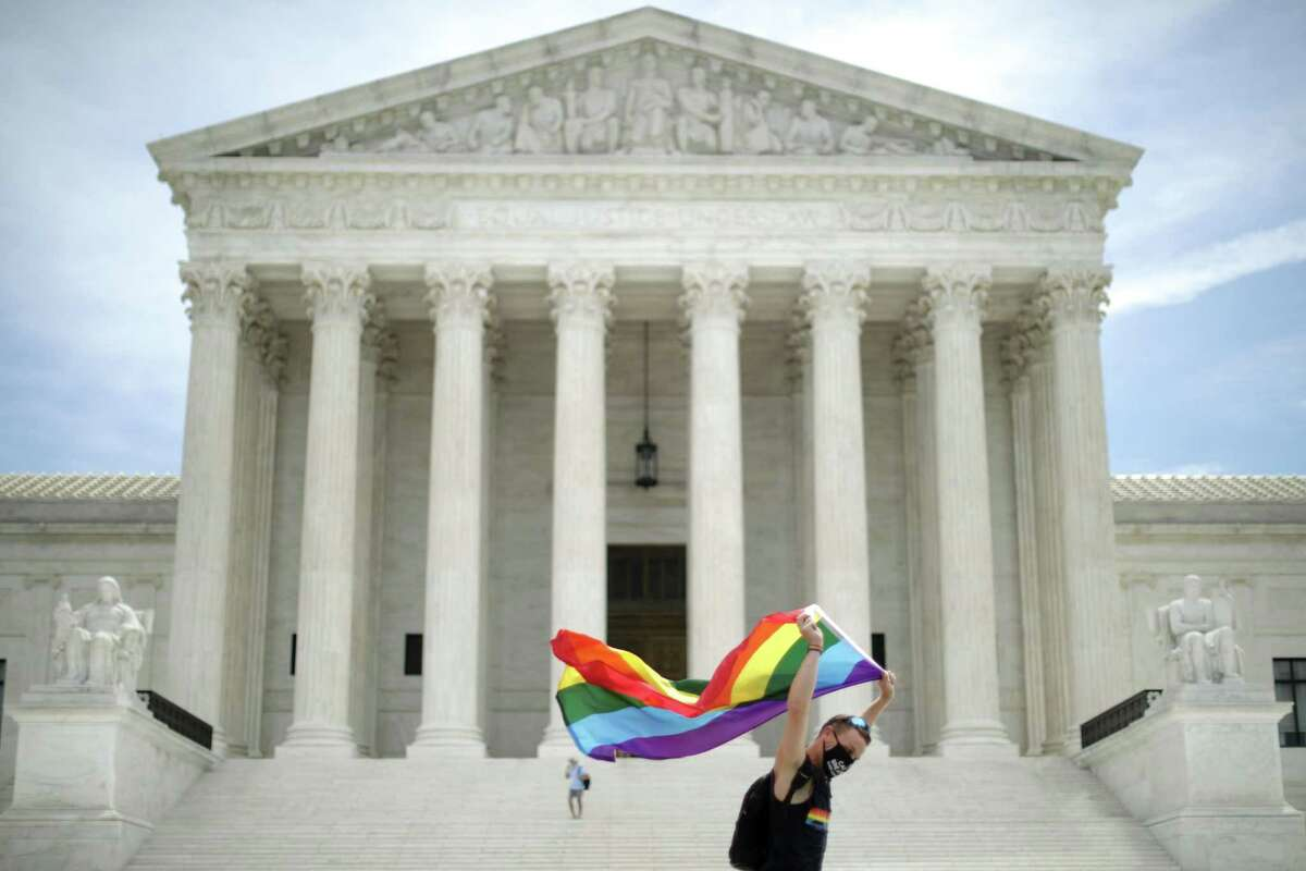 Joseph Fons holding a Pride Flag, walks back and forth in front of the U.S. Supreme Court building after the court ruled that LGBTQ people can not be disciplined or fired based on their sexual orientation June 15, 2020 in Washington. With Chief Justice John Roberts and Justice Neil Gorsuch joining the Democratic appointees, the court ruled 6-3 that the Civil Rights Act of 1964 bans bias based on sexual orientation or gender identity.