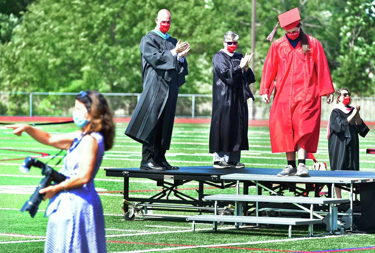 """Branford, Connecticut - Monday, June 15, 2020: Branford High School holds a """"drive-through"""" graduation Monday morning on the Branford High School football field. Families arrive in cars, wait in line to drive up to the field, at which time students will get out and go out to a stage in the center of the field to receive their diplomas. Families are allowed to briefly exit their cars to take photographs of their high school graduates."""