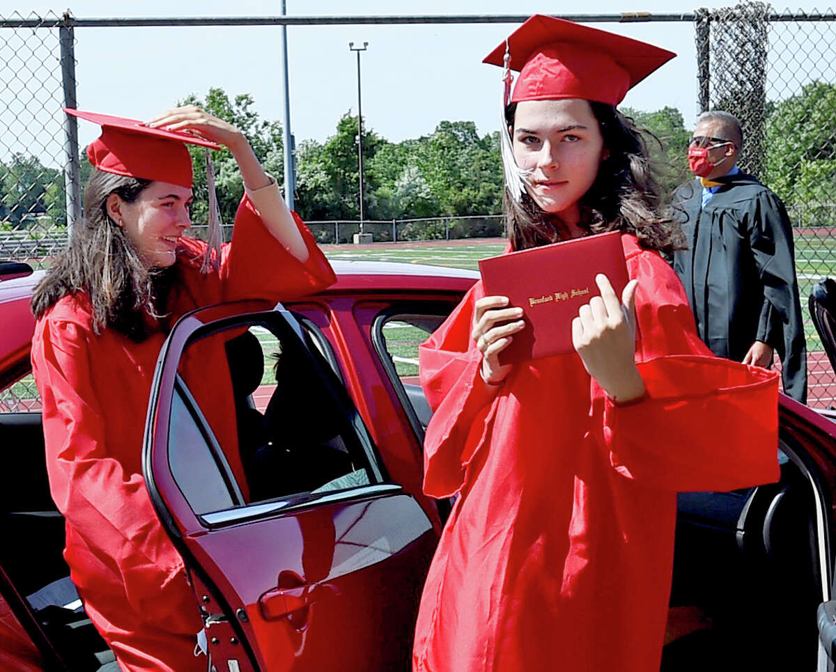 """Branford, Connecticut - Monday, June 15, 2020: Adrienne and Julianne Dillon return to their cars after receiving their diplomas as Branford High School holds a """"drive-through"""" graduation Monday morning on the Branford High School football field. Families arrive in cars, wait in line to drive up to the field, at which time students will get out and go out to a stage in the center of the field to receive their diplomas. Families are allowed to briefly exit their cars to take photographs of their high school graduates."""