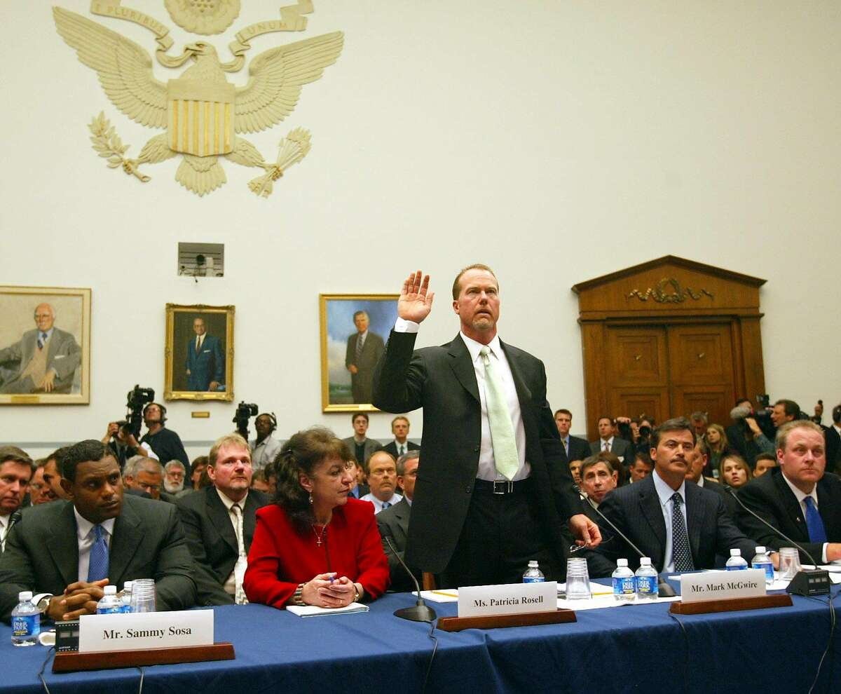 ** FILE ** Former baseball player Mark McGwire is sworn in before testifying at a hearing on Capitol Hill on the use of steroids in professional baseball in Washington, in this March 17, 2005 file photo. From left, Baltimore Orioles' Sammy Sosa, his interpreter Patricia Rosell, McGwire, Orioles' Rafael Palmiero and Boston Red Sox Curt Schilling. (AP Photo/Gerald Herbert)