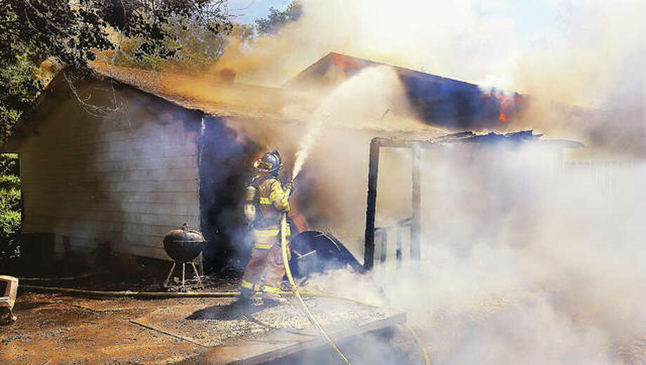 An Edwardsville firefighter uses a hose line on the rear of a house Monday in the 3400 block of Glennoak Drive in rural Edwardsville. A 70-year-old man reportedly was found deceased at the home as firefighters were extinguishing a fire at the rear of the house that spread to the house itself, causing extensive damage. Firefighters from Edwardsville, Wood River, Glen Carbon, Holiday Shores and Hamel responded to the scene. Photo: John Badman   Hearst Newspapers