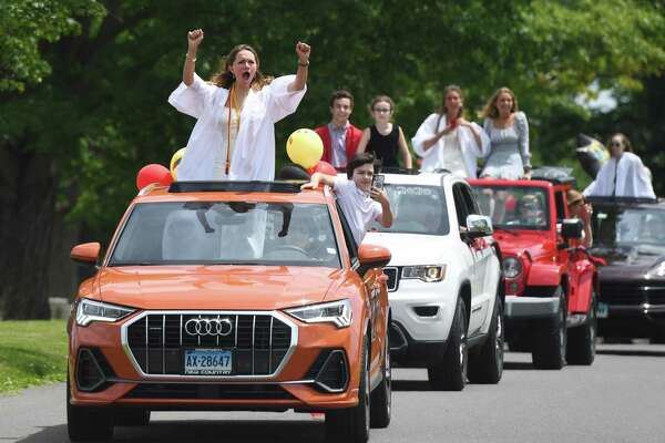 Christina Poterova and other new graduates celebrate during the New Canaan High School Class of 2020 drive-thru graduation parade at Waveny Park in New Canaan on Monday. The 301 graduates of New Canaan's Class of 2020 took a raucous ride through town with their families as teachers waited to congratulate them for their achievements as they passed through Waveny Park.