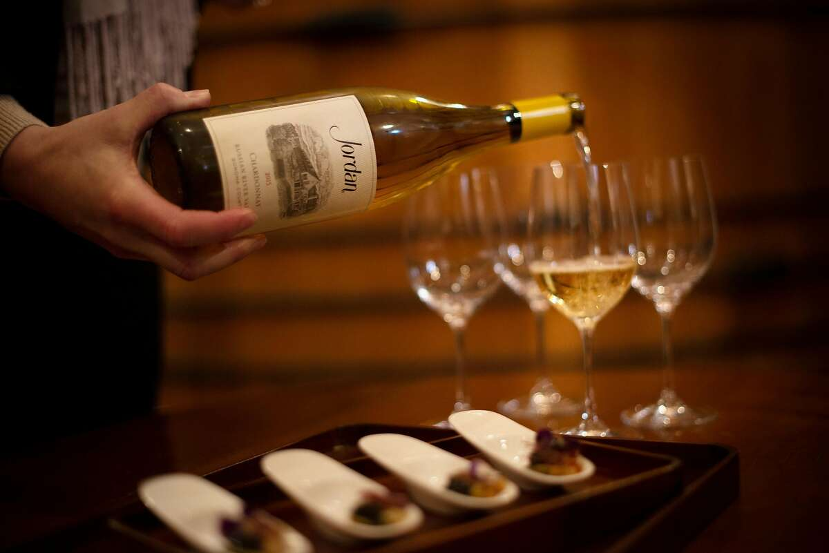 A bottle of 2015 Chardonnay is poured next to servings of abalone poke with caviar prepared by Executive Chef Todd Knoll at Jordan Vineyard & Winery in Healdsburg, California. January 9, 2019.