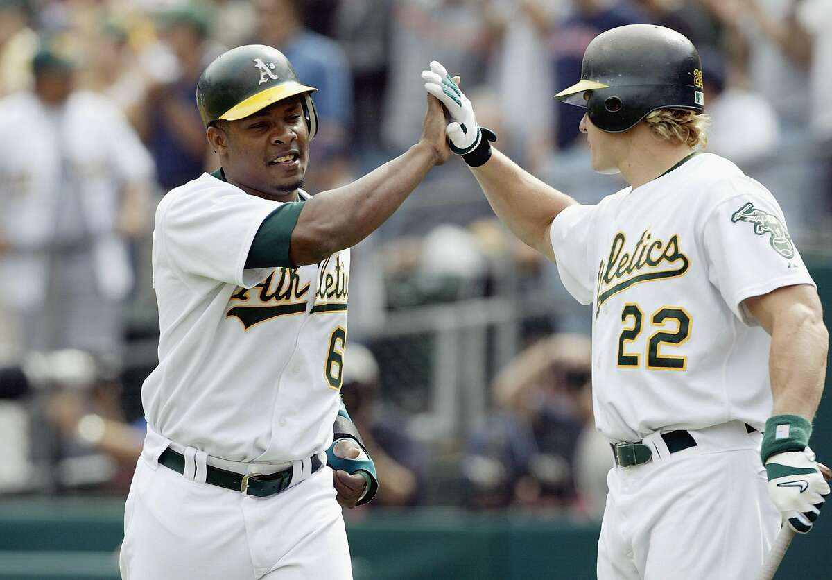 OAKLAND, CA - OCTOBER 2: Jose Guillen #6 of the Oakland A's celebrates the first run of the game against the Boston Red Sox with teammate Eric Byrnes #22 during the second inning of Game 2 of the 2003 American League Division Series on October 2, 2003 at Network Associates Coliseum in Oakland, California. The A's defeated the Red Sox 5-1.