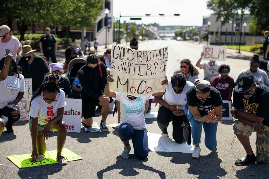 Demonstrators kneel for two minutes in downtown Conroe in honor of George Floyd, Sunday, June 14, 2020. An estimated 70 demonstrators participated in the march organized by Good Brothers & Sisters of Montgomery County, a new community organization. Good Brothers & Ssiters will be hosting a Juneteenth event this Friday at MLK Park. Photo: Gustavo Huerta, Houston Chronicle / Staff Photographer / Houston Chronicle © 2020
