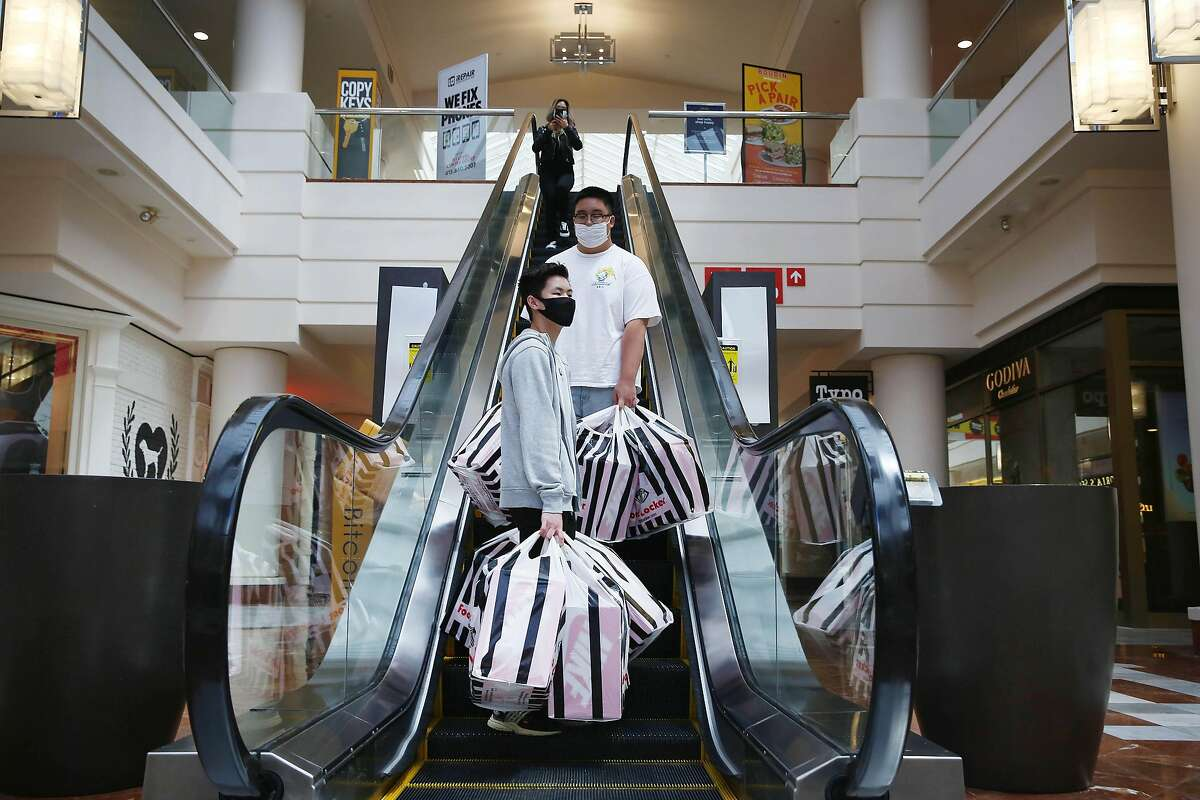 With San Francisco's rising number of coronavirus hospitalizations, malls such as Stonestown (seen here), Japantown, and Westfield will have to close. Chris Wu (front), 16 and Tyler Kan (second from front), both of San Francisco, carry shopping bags of sneakers after making a purchase for their basketball team fundraiser at Stonestown Mall on Monday, June 15, 2020 in San Francisco, Calif.