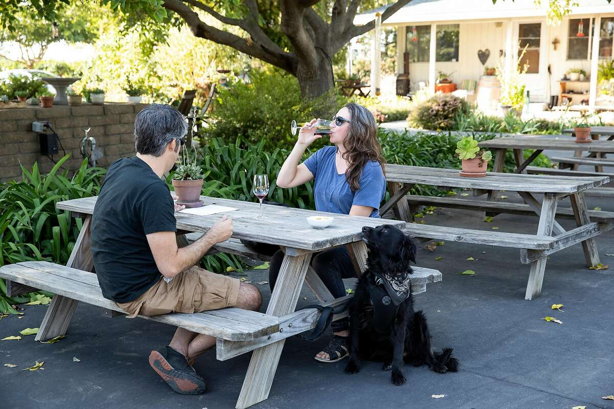 Vasco Asturiano and Susannah Gray wine taste outside with their dog Che at Heritage Oak Winery in Acampo, Calif., on Saturday, September 28, 2019. The winery property includes picnic tables and hiking trails in addition to a tasting room.