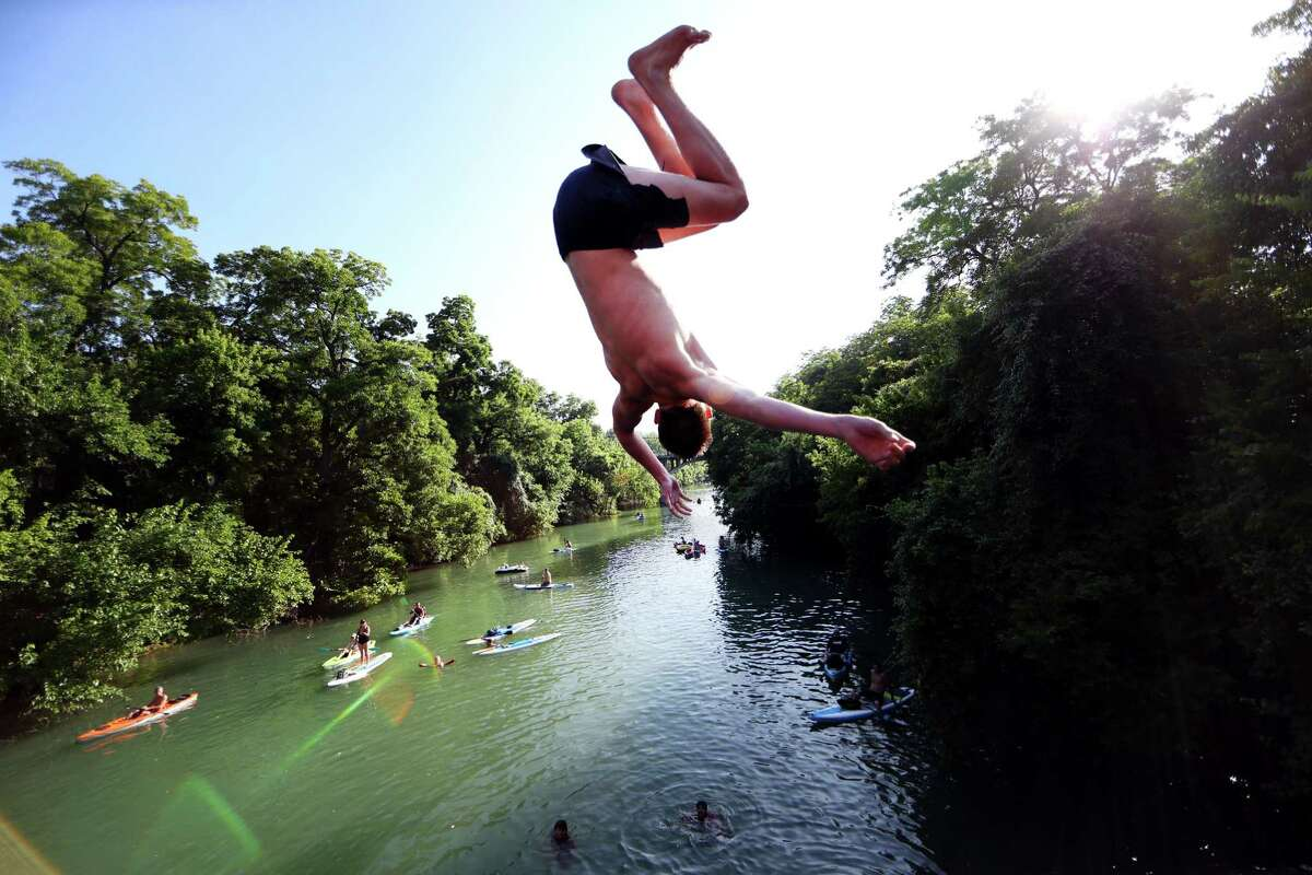 Swimmers jump off a bridge into Austin's Barton Creek, as paddle boarders and kayakers look on.