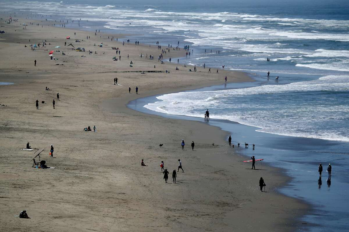 People walk along Ocean Beach on May 26, 2020 in San Francisco. The spread of the coronavirus may be contained during the summer as people spend more time outdoors, experts say.