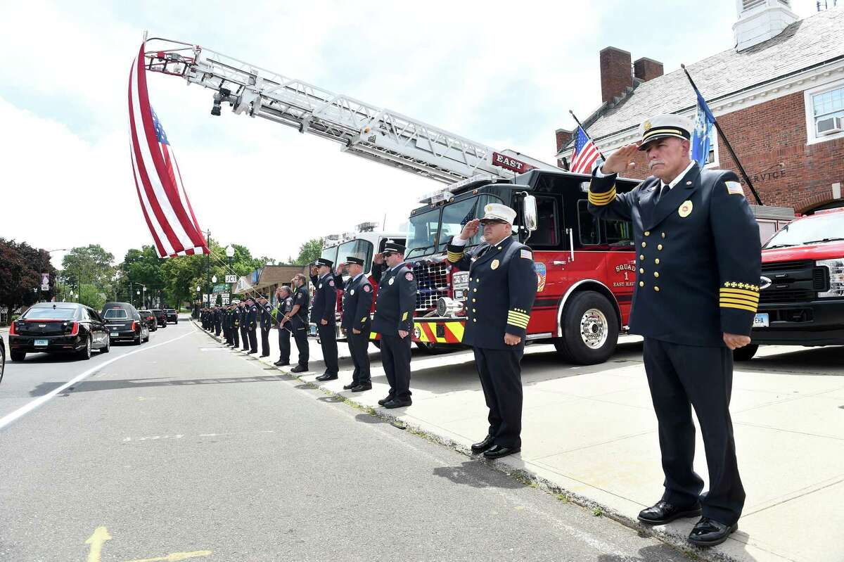 """East Haven firefighters salute in formation as the funeral procession of former East Haven Mayor Henry """"Hank"""" Luzzi passes the East Haven Fire Department Engine Company #1 on Main Street in East Haven on June 15, 2020. Second from right is East Haven Fire Chief Matthew Marcarelli and at far right is Assistant Chief Charles Licata."""