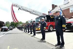 "East Haven firefighters salute in formation as the funeral procession of former East Haven Mayor Henry ""Hank"" Luzzi passes the East Haven Fire Department Engine Company #1 on Main Street in East Haven on June 15, 2020. Second from right is East Haven Fire Chief Matthew Marcarelli and at far right is Assistant Chief Charles Licata."