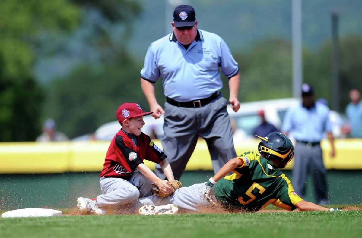 An umpire watches as Nate Klein tags Northwest runner Ryan Lacey at third base during Fairfield American's first game of the Little League World Series in Williamsport, Penn., on Friday, August 20, 2010.
