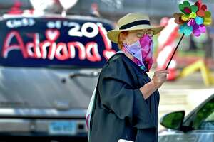 "Branford, Connecticut - Monday, June 15, 2020: Fine arts teacher Donna Roy cheers on seniors as Branford High School holds a ""drive-through"" graduation Monday morning on the Branford High School football field. Families arrive in cars, wait in line to drive up to the field, at which time students will get out and go out to a stage in the center of the field to receive their diplomas. Families are allowed to briefly exit their cars to take photographs of their high school graduates."