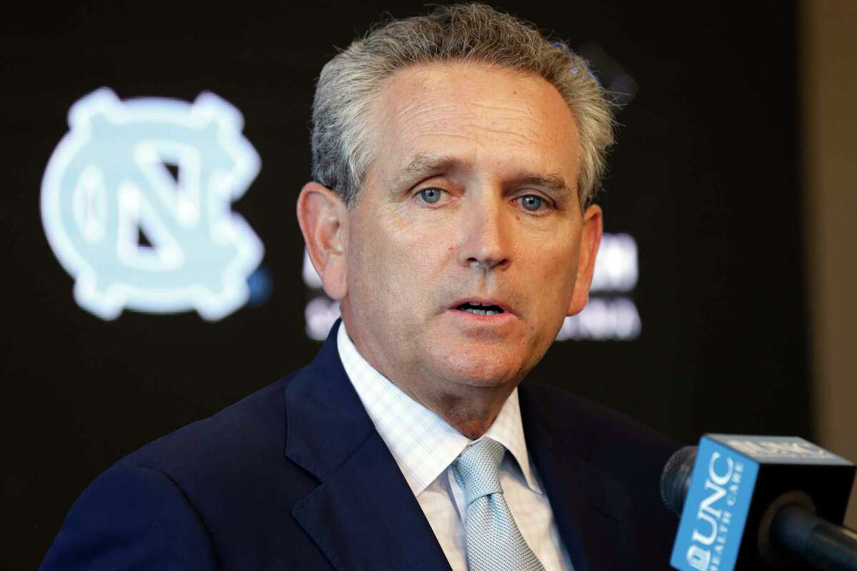 """FILE - In this Aug. 6, 2018, file photo, University of North Carolina athletic director Bubba Cunningham makes comments during the NCAA college football team's media day in Chapel Hill, N.C. More than a dozen national associations in various sports a€?"""" hockey, soccer, tennis, golf, swimming and gymnastics, among them a€?"""" have signed a memo outlining a€œsignificant concernsa€ about effects of allowing athletes to profit for use of their names, images and likenesses (NIL). The memo, prepared by North Carolina athletics director Bubba Cunningham and associate athletics director Paul Pogge, was sent last week to a law committee examining whether to craft a standardized athlete-compensation law for states to adopt. (AP Photo/Gerry Broome, File)"""