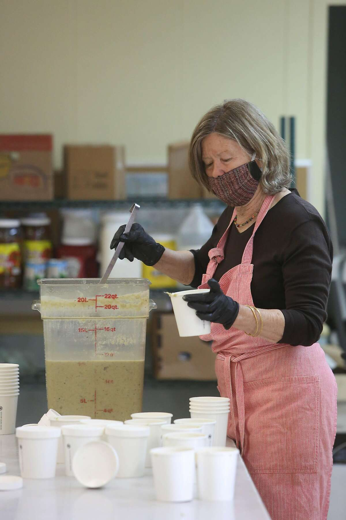 Anne Hatch, Food Runner volunteer, prepares food for delivery as she works in the new Food Runners' kitchen at the Waller Center in San Franciscon Monday, April 20, 2020 in San Francisco, Calif.
