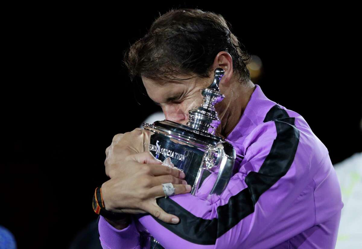 FILE - In this Sept. 8, 2019, file photo, Rafael Nadal, of Spain, hugs the trophy after defeating Daniil Medvedev, of Russia, to win the men's singles final of the U.S. Open tennis championships in New York. The U.S. Tennis Association intends to hold the U.S. Open Grand Slam tournament in New York starting in August without spectators, if it gets governmental support -- and a formal announcement could come this week. (AP Photo/Adam Hunger, File)