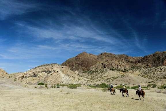 Horseback riders pass through Rough Run Creek in Terlingua.
