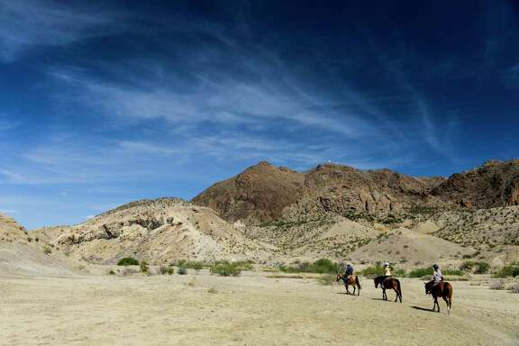 Big skies and horses are part of the myth of Texas. Horseback riders pass through Rough Run Creek outside Big Bend National Park