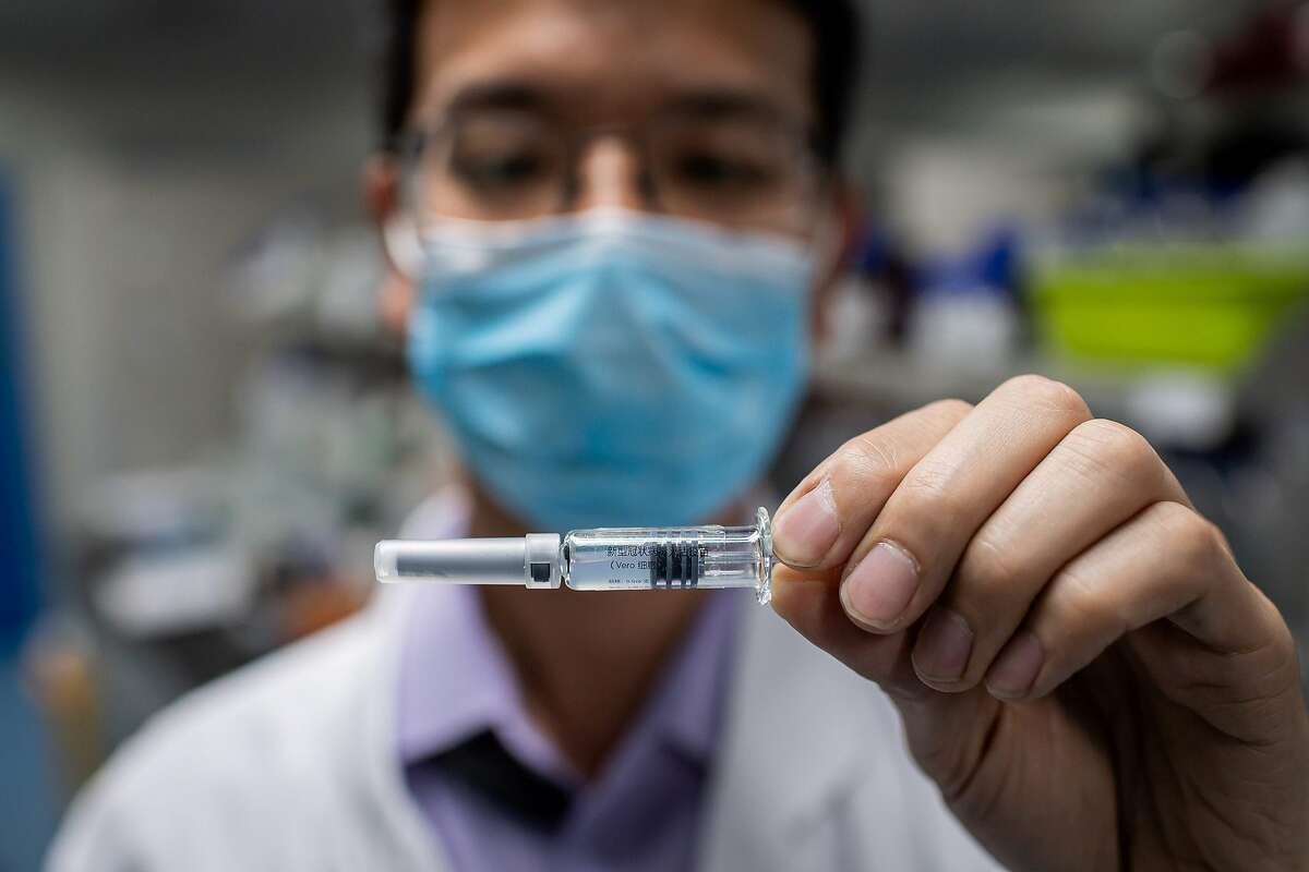 An engineer displays an experimental vaccine for the COVID-19 during testing at the Quality Control Laboratory at Sinovac Biotech facilities in Beijing in this April file photo. A total of 27 drugmakers are working on vaccines for the disease.