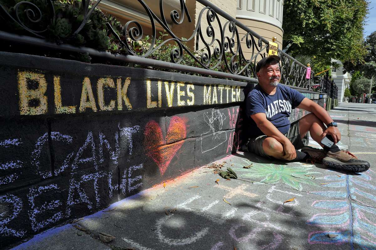 James Juanillo sits on the sidewalk outside his home which has been covered in supportive chalk art in San Francisco, Calif., on Monday, June 15, 2020. Juanillo hoped to inspire others when he started stenciling