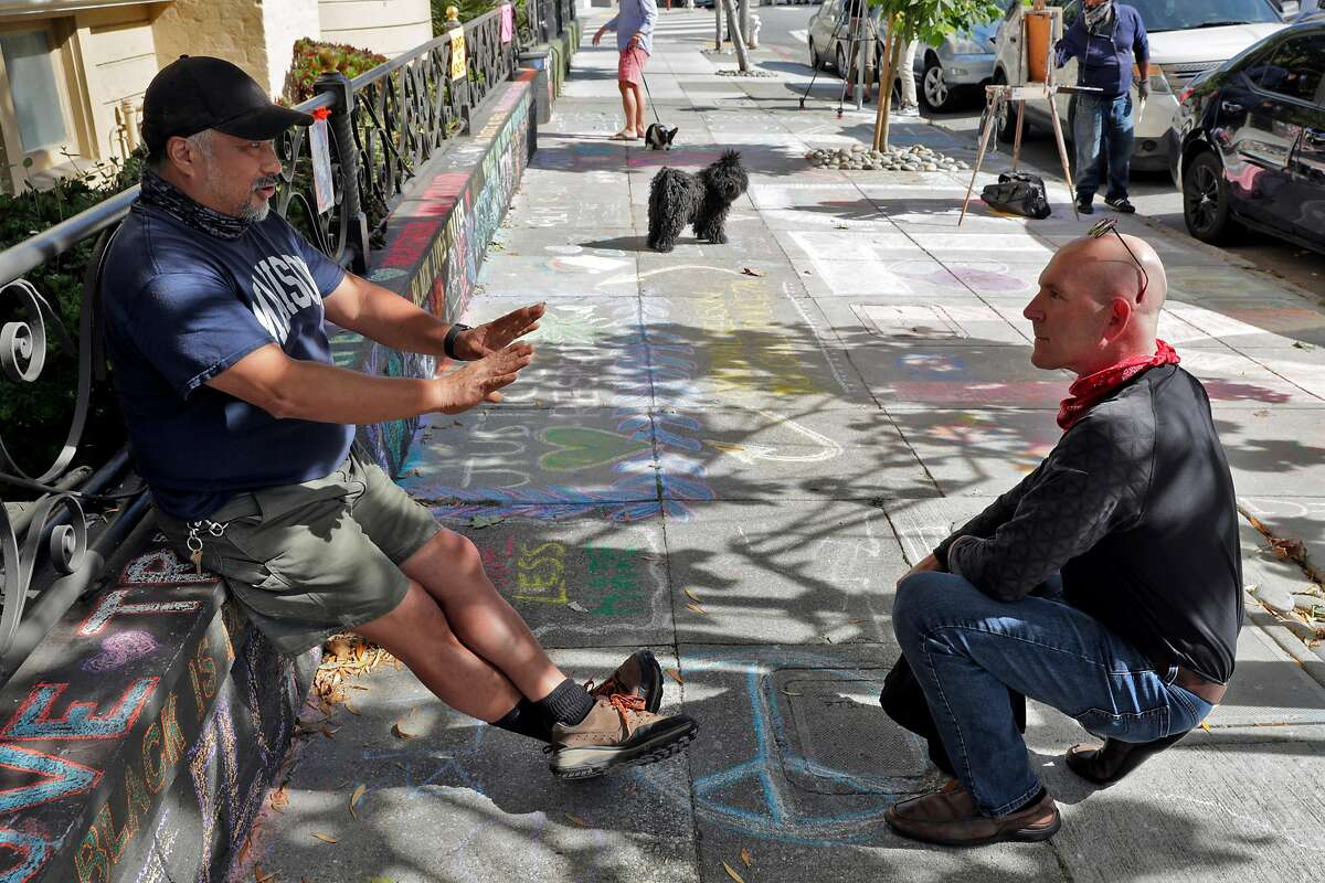 James Juanillo, left, talks to a sympathetic passerby on the sidewalk outside the home which has been covered in supportive chalk art in San Francisco, Calif., on Monday, June 15, 2020. Juanillo hoped to inspire others when he started stenciling