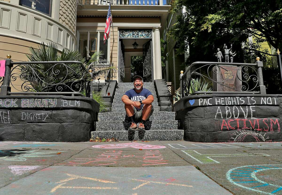James Juanillo sits on the steps outside the home which has had the sidewalk covered in supportive chalk art in San Francisco, Calif., on Monday, June 15, 2020. Juanillo hoped to inspire others when he started stenciling