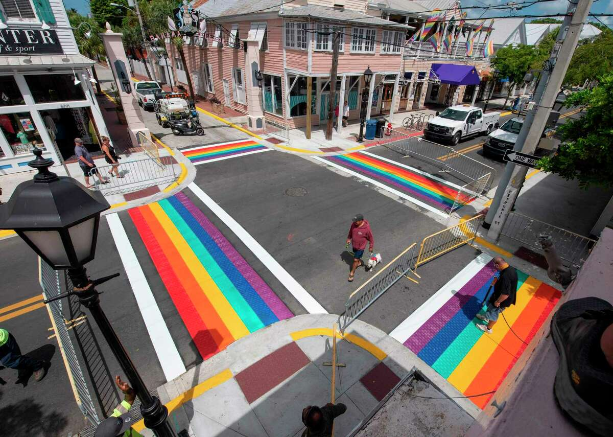 """This handout photo released by the Florida Keys News Burean shows a man walking a dog as Paul Cassidy (R), a Key West Public Works foreman, uses a propane torch to embed thermoplastic strips representing a rainbow flag into the asphalt, June 15, 2020, in Key West, Florida. - Installation of the rainbow crosswalks capped a project to repave most of Key Wests historic Duval Street. The rainbow flag is a recognized symbol of LGBTQ unity. (Photo by Rob O'Neal / Florida Keys News Bureau / AFP) / RESTRICTED TO EDITORIAL USE - MANDATORY CREDIT """"AFP PHOTO / FLORIDA KEYS NEWS BUREAU / ROB O'NEAL """" - NO MARKETING - NO ADVERTISING CAMPAIGNS - DISTRIBUTED AS A SERVICE TO CLIENTS (Photo by ROB O'NEAL/Florida Keys News Bureau/AFP via Getty Images)"""