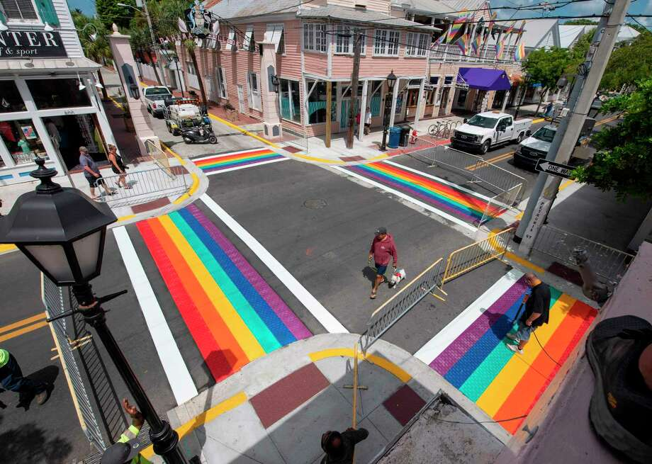 """This handout photo released by the Florida Keys News Burean shows a man walking a dog as Paul Cassidy (R), a Key West Public Works foreman, uses a propane torch to embed thermoplastic strips representing a rainbow flag into the asphalt, June 15, 2020, in Key West, Florida. - Installation of the rainbow crosswalks capped a project to repave most of Key Wests historic Duval Street. The rainbow flag is a recognized symbol of LGBTQ unity. (Photo by Rob O'Neal / Florida Keys News Bureau / AFP) / RESTRICTED TO EDITORIAL USE - MANDATORY CREDIT """"AFP PHOTO / FLORIDA KEYS NEWS BUREAU / ROB O'NEAL """" - NO MARKETING - NO ADVERTISING CAMPAIGNS - DISTRIBUTED AS A SERVICE TO CLIENTS (Photo by ROB O'NEAL/Florida Keys News Bureau/AFP via Getty Images) Photo: ROB O'NEAL, Contributor / Florida Keys News Bureau/AFP Via Getty Images / AFP"""