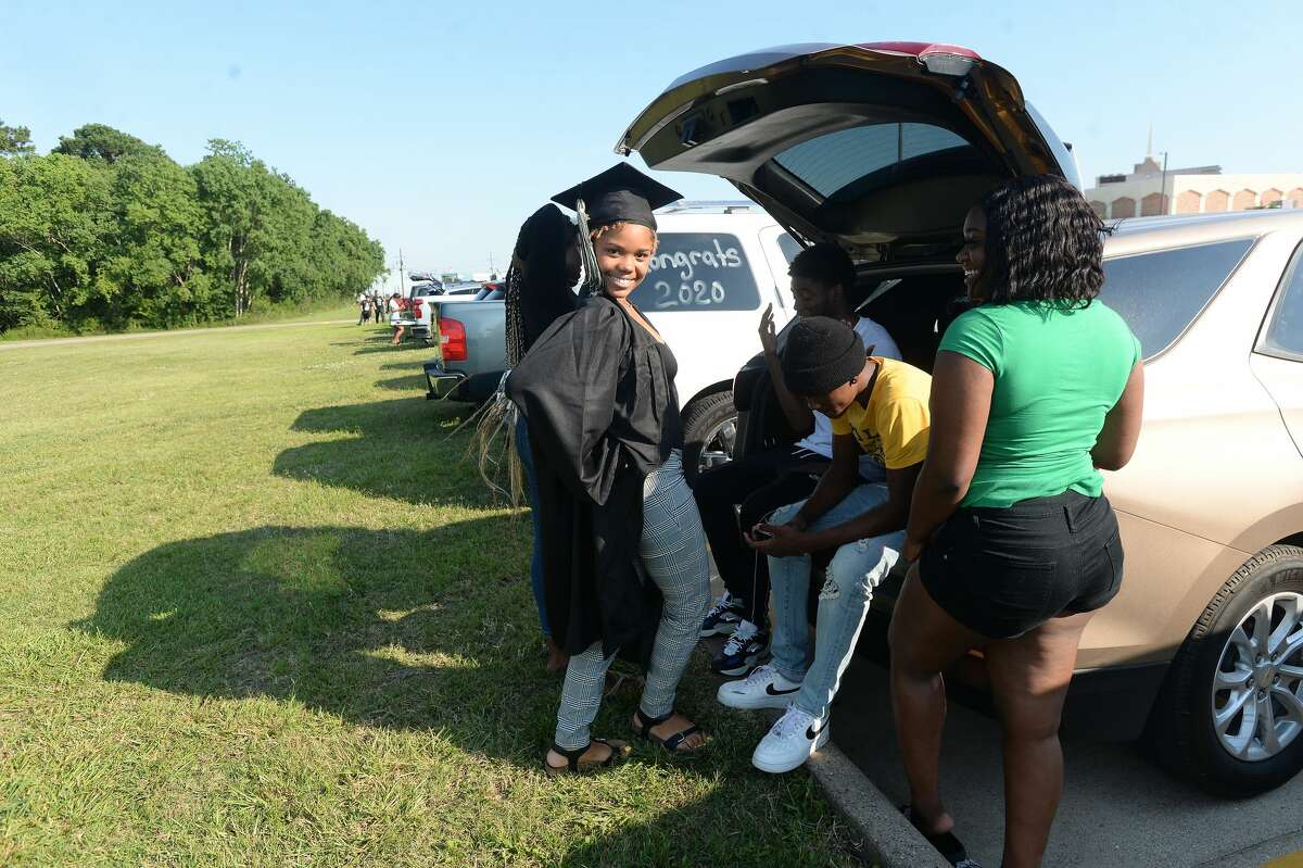 Graduate Latovia Miller celebrates with family as Evolution Academy graduates its 7th senior class at its Beaumont campus during an outdoor drive-up ceremony at the school Monday. Photo taken Monday, June 15, 2020 Kim Brent/The Enterprise