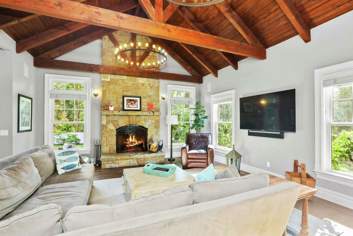 The main-level family room is a dramatic space, with a vaulted, beamed ceiling and double-height fieldstone fireplace. A tour of the first floor begins at the charming covered front porch. Inside the main entrance, a foyer with magnificent herringbone hardwood flooring provides the pathway to the public rooms - a library to the left and the formal living room to the right. The living room, in turn, opens to the formal dining room and onward to the back-of-the house family room, which seamlessly opens to the breakfast room and kitchen. A few of the architectural detail buyers will find among these spaces are bay windows in the library, living room and dining room. In the family room, there's a two-story fieldstone fireplace. One of the six bedrooms is positioned on the first floor, as well. It has an en-suite full bath. There's also a convenient powder room just off the foyer. The bathrooms throughout the house are adorned in marble, granite or limestone.