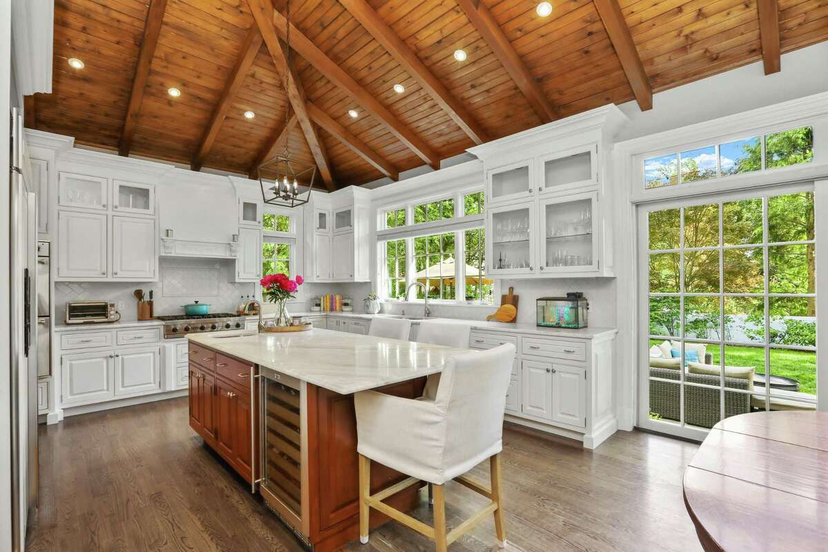 The vaulted ceiling carries through to the eat-in kitchen that opens seamlessly to the family room. The space is bright and inviting, with oversized windows, white cabinetry, and a blend of task and decorative lighting. Asked to describe the personality of the house, the homeowner defined it as