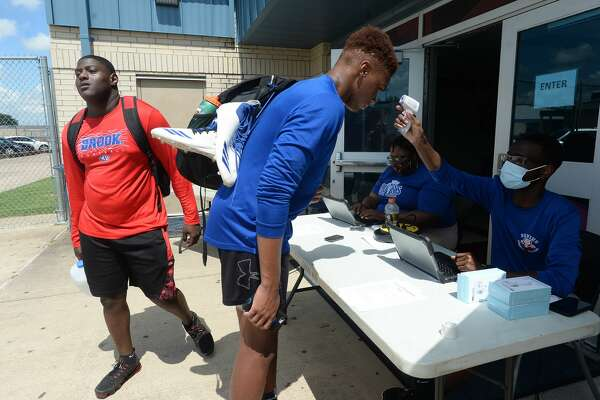 Athletes have their temperatures taken as they check in on the first day of summer conditioning at West Brook Monday morning. While most schools started the summer workouts when the state permitted last week, BISD programs waited until this week to hold camps. Photo taken Monday, June 15, 2020 Kim Brent/The Enterprise