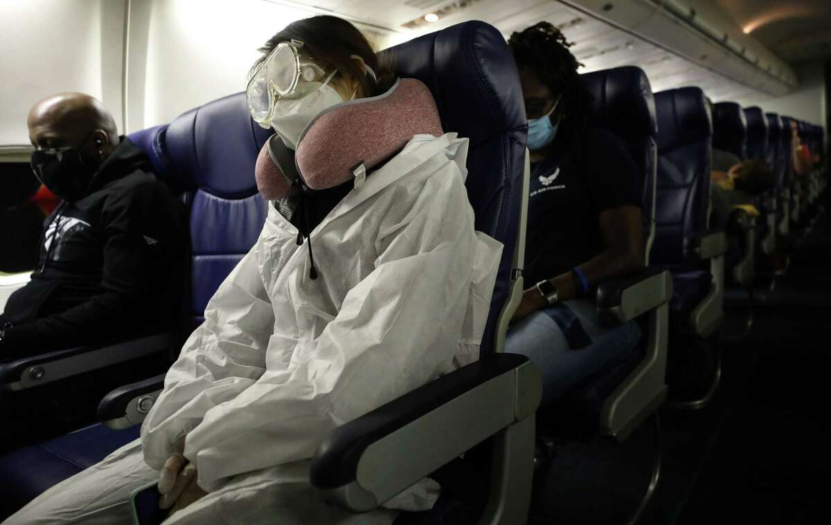 A passenger wears personal protective equipment (PPE) while aboard a Southwest Airlines flight from Los Angeles, California to Houston, Texas on June 7, 2020. All passengers were required to wear face coverings and middle seats were left unoccupied to allow for social distancing.