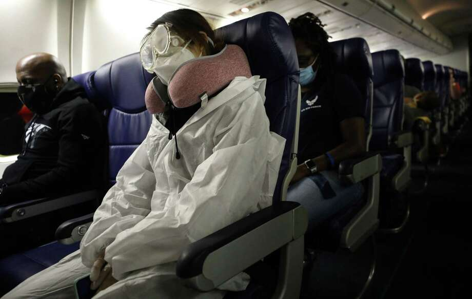 A passenger wears personal protective equipment (PPE) while aboard a Southwest Airlines flight from Los Angeles, California to Houston, Texas on June 7, 2020. All passengers were required to wear face coverings and middle seats were left unoccupied to allow for social distancing. Photo: Mario Tama, Staff / Getty Images / 2020 Getty Images