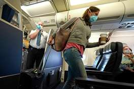 A passenger wears a mask while boarding a United Airlines flight at George Bush Intercontinental Airport Sunday, May 24, 2020, in Houston. Fewer people are flying this Memorial Day holiday amid the COVID-19 coronavirus pandemic.