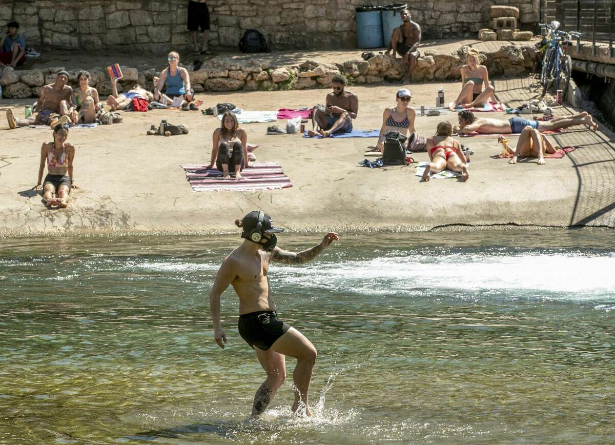 Kristopher McCoy frolics in the cool waters of Barton Creek on Wednesday March 25, 2020. Dozens of people gathered at Barton Creek below the dam at Barton Springs Pool on the first day of the shelter in place order in Austin due to the coronavirus pandemic.